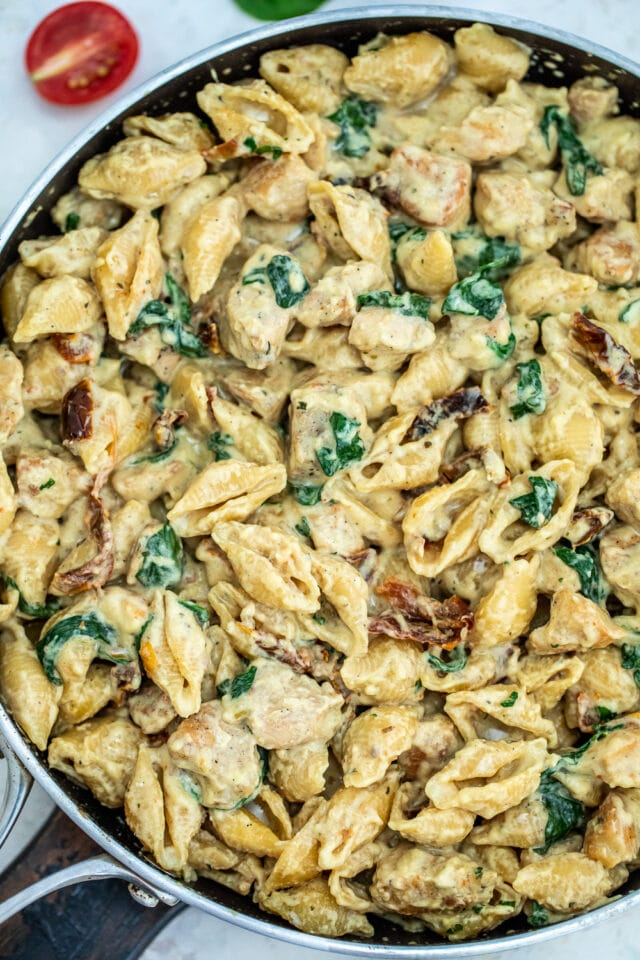 Tuscan Chicken Pasta is a quick and easy one-pan dish made with crispy chicken, sun-dried tomatoes, shell pasta, and soaked in a creamy white sauce. #pasta #tuscanchicken #chickenrecipes #30minutemeals #onepotmeals
