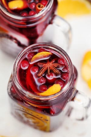 Orange Cranberry Sangria bursts with flavors reminiscent of autumn and winter! This makes for the perfect cocktail for upcoming holidays, with hints of orange and spices! #sangria #cranberrysangria #30minutemeals #fallrecipes #thanksgiving #christmas