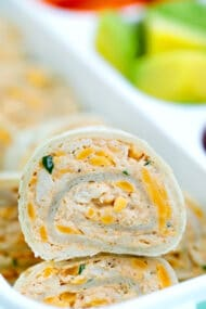 These Taco Tortilla Roll Ups are made with shredded chicken, cream cheese, taco seasoning, and cheddar cheese. #rollups #pinwheels #taco #partyfood #30minutemeals