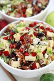 Brussels Sprouts Salad is a quick and easy side dish made with shredded brussels sprouts, crispy apples, cranberries, pomegranate arils, feta cheese, and pecans. #salad #thanksgiving #christmasrecipes #sidedish #30minutemeals