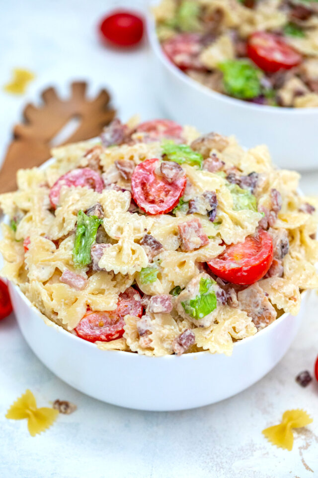 Chicken Caesar Pasta Salad is a refreshing dish made with chicken, bow tie pasta, Parmesan cheese, grape tomatoes, and bacon, all tossed in a creamy Caesar dressing. #chickencaesar #pastasalad #pastarecipes #potluckrecipes #30minutemeals