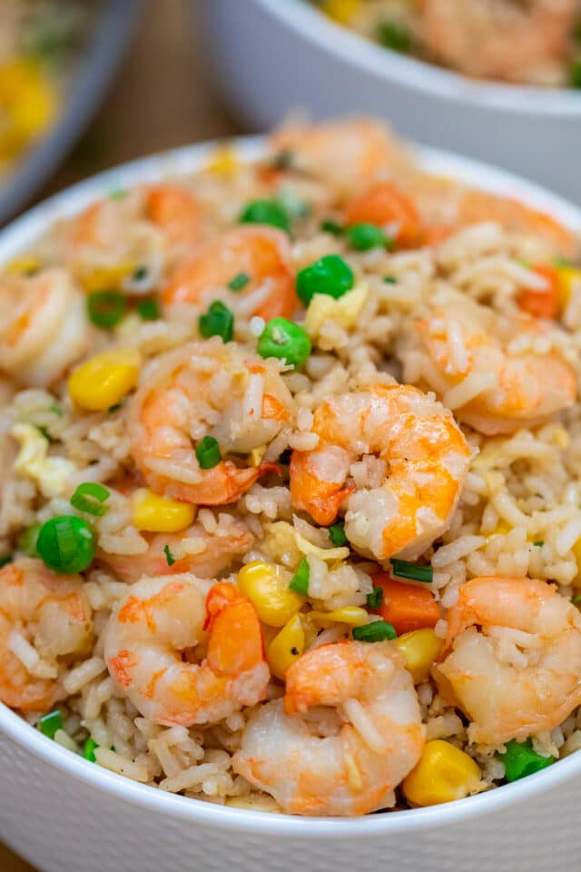 Shrimp Fried Rice recipe is made with fresh shrimp, rice, green onions, peas, carrots, and sesame oil. It is a classic dinner dish that is ready in about 30 minutes! #friedrice #shrimprecipes #30minutemeals #shrimpfriedrice #chineserecipes