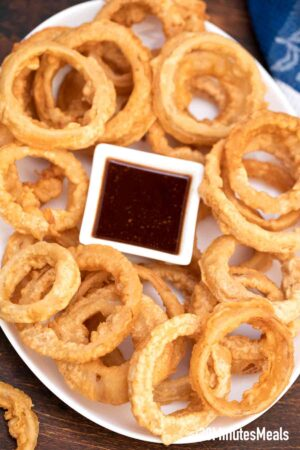 beer battered onion rings on a plate with dipping sauce