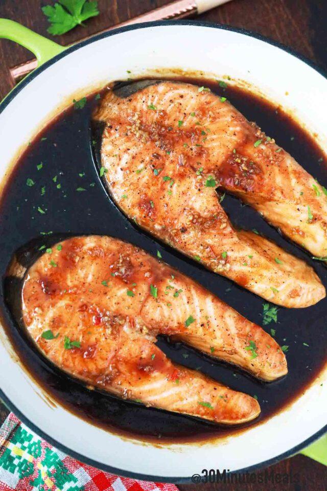 salmon steaks in sauce in a pan